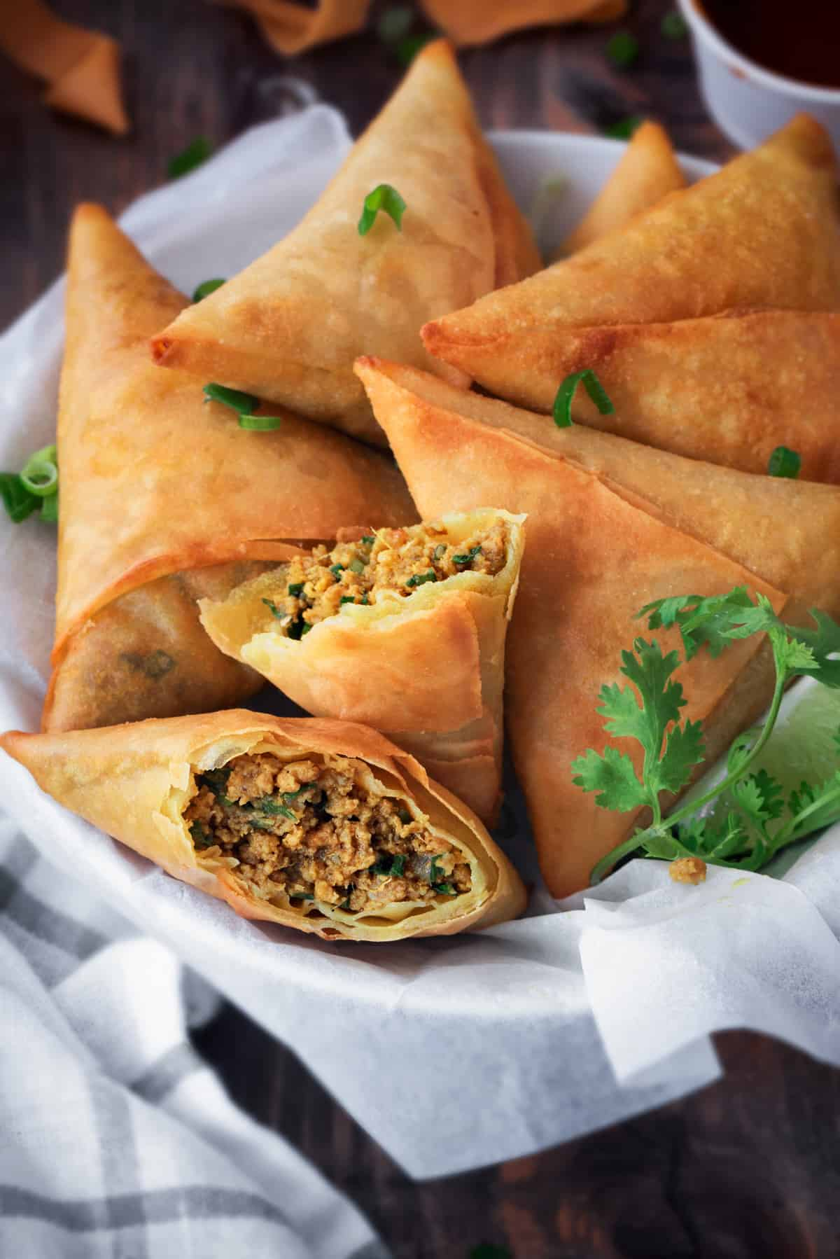 Crisp Mutton Keema Samosa served in basket, one samosa cut open to show the within.