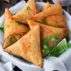 linen lined bowl filled with 5 fried keema samosa with fresh cilantro and a lime wedge