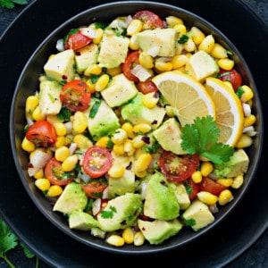 Fresh tomato avocado corn salad served in black plate, some cilantro spread around.