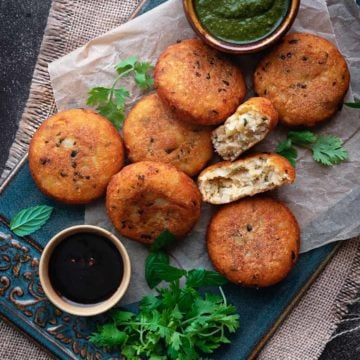 Crispy aloo tikki with one patty open served with chutney on blue ceramic tray.