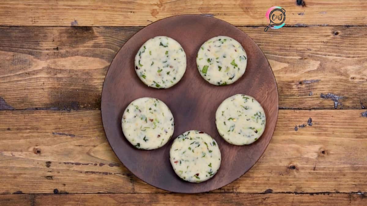 5 shaped aloo tikkis or patties placed on a wooden plate.