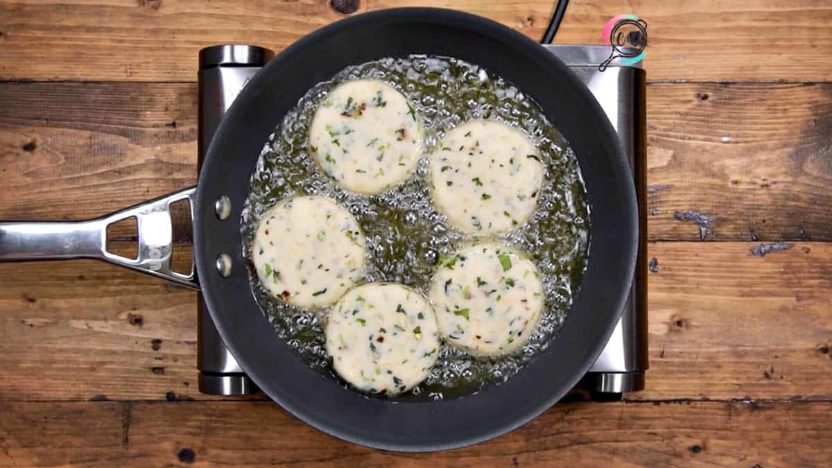 5 patties shallow frying in oil in pan.