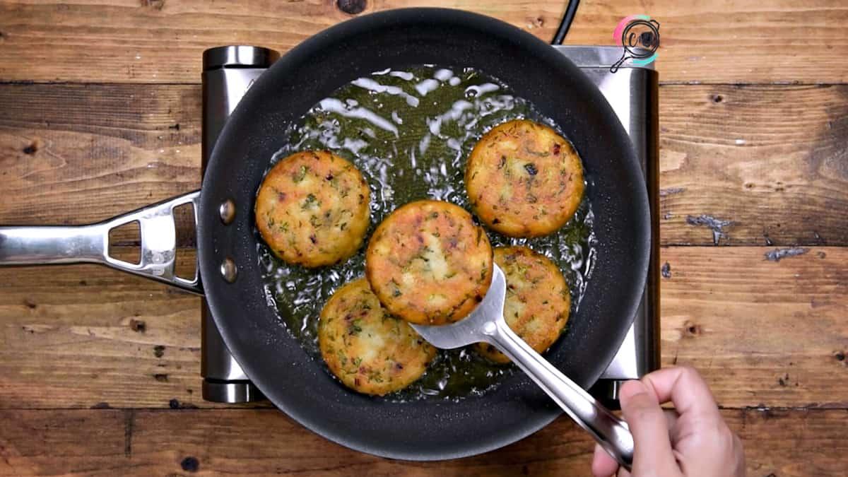 Golden fried crisp aloo tikki in pan, ready to serve.
