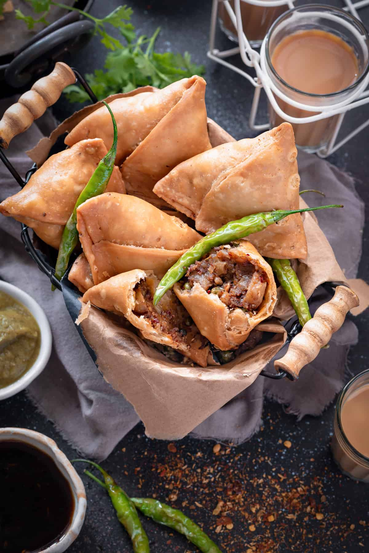 Flaky samosas in basket with one samosa cut open to show the filling within.