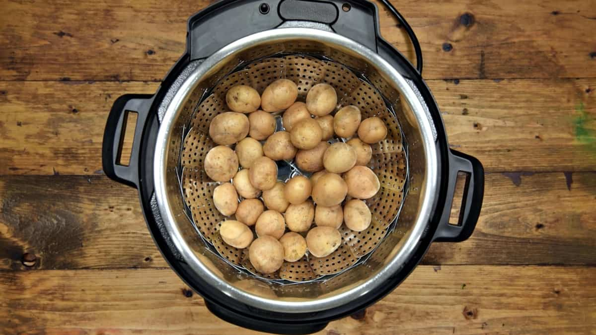 Baby potatoes added in steamer basket placed in the steel insert of Instant Pot.
