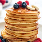 Stack of homemade Fluffy Pancakes topped with berries, banana slices and maple syrup.