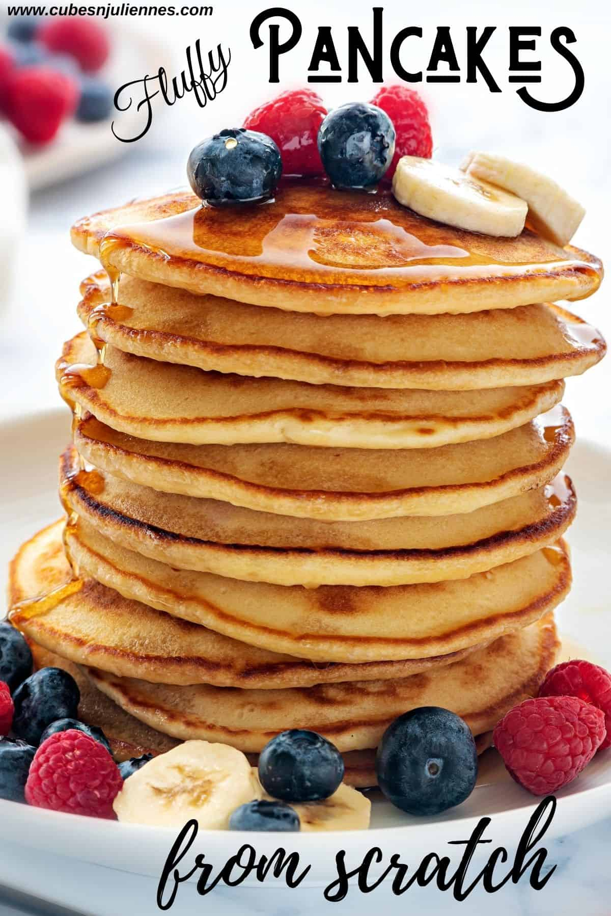 Close up shot of stacked pancakes topped with maple syrup, berries and banana slices.