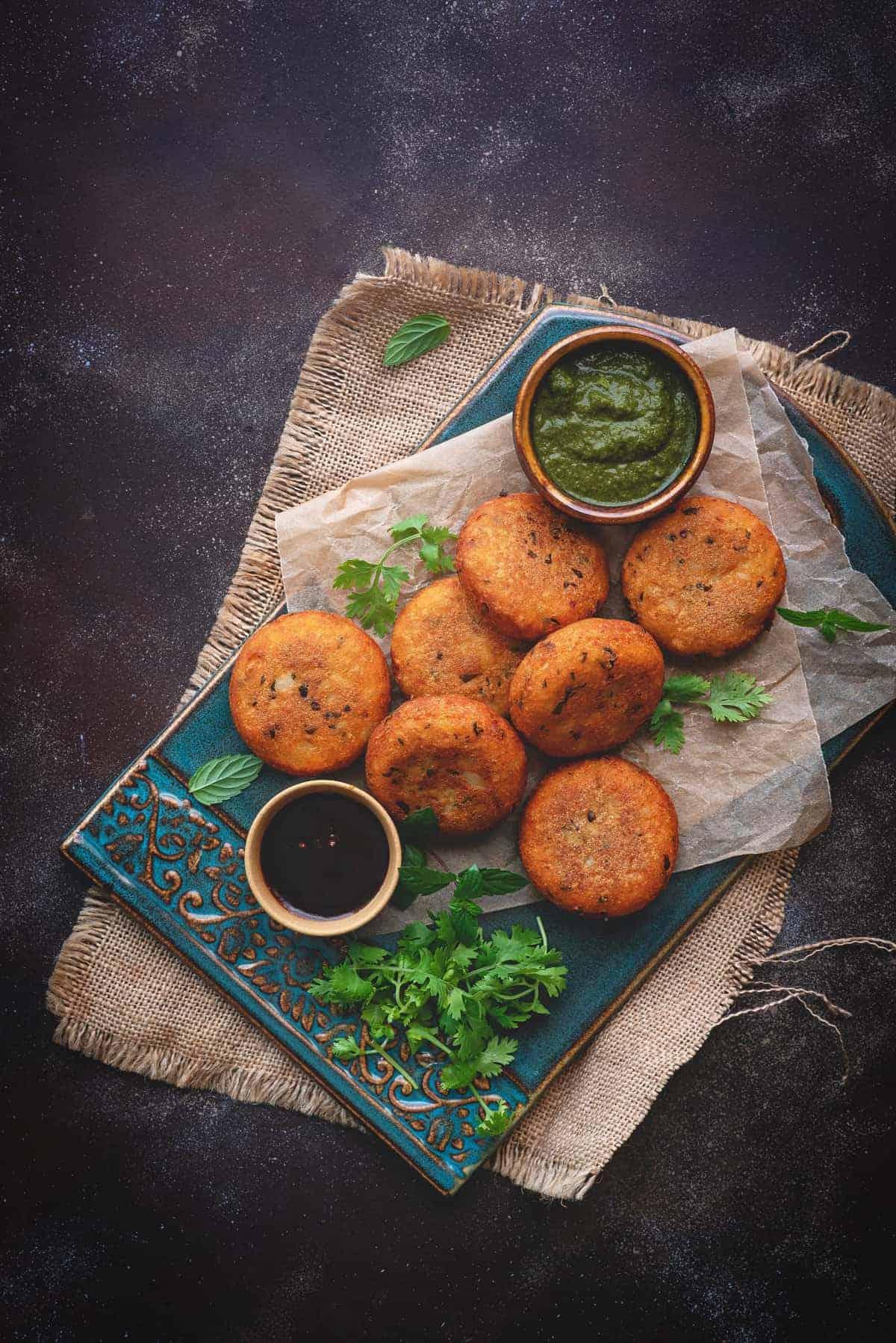 Crispy aloo patties served on  blue ceramic tray, chutney in bowls on side.