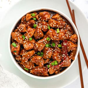 Instant Pot General Tso Chicken gravy served in white bowl with a pair of chopsticks.