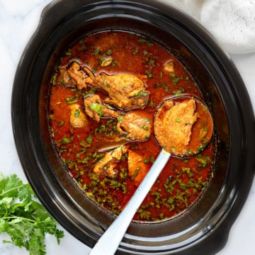 Indian chicken curry in slow cooker pot with a ladle into it holding chicken piece.