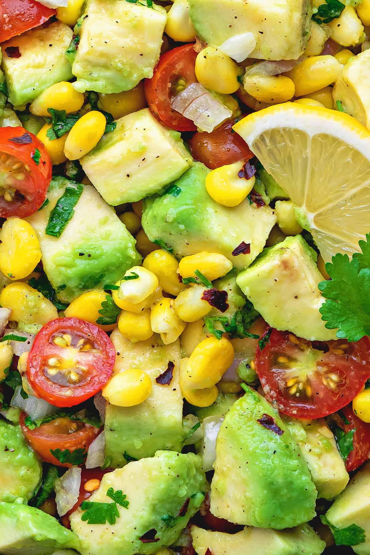 Close up shot of tomato corn and avocado salad.