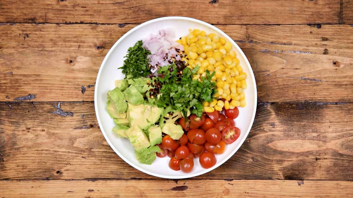 Tomato, corn kernels, onion, diced avocado, chopped parsley, cilantro and chilli flakes added in white bowl.