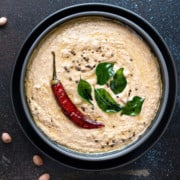 Close up shot of Peanut chutney in black bowl with few groundnut seeds spread around.