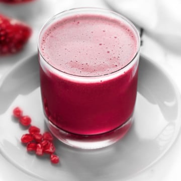 Homemade Pomegranate juice served in glass, few arils spread around.