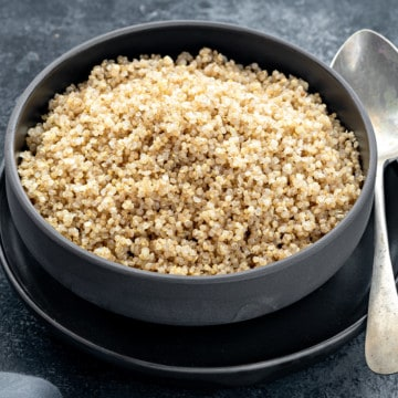 Close up shot of cooked quinoa in black bowl.