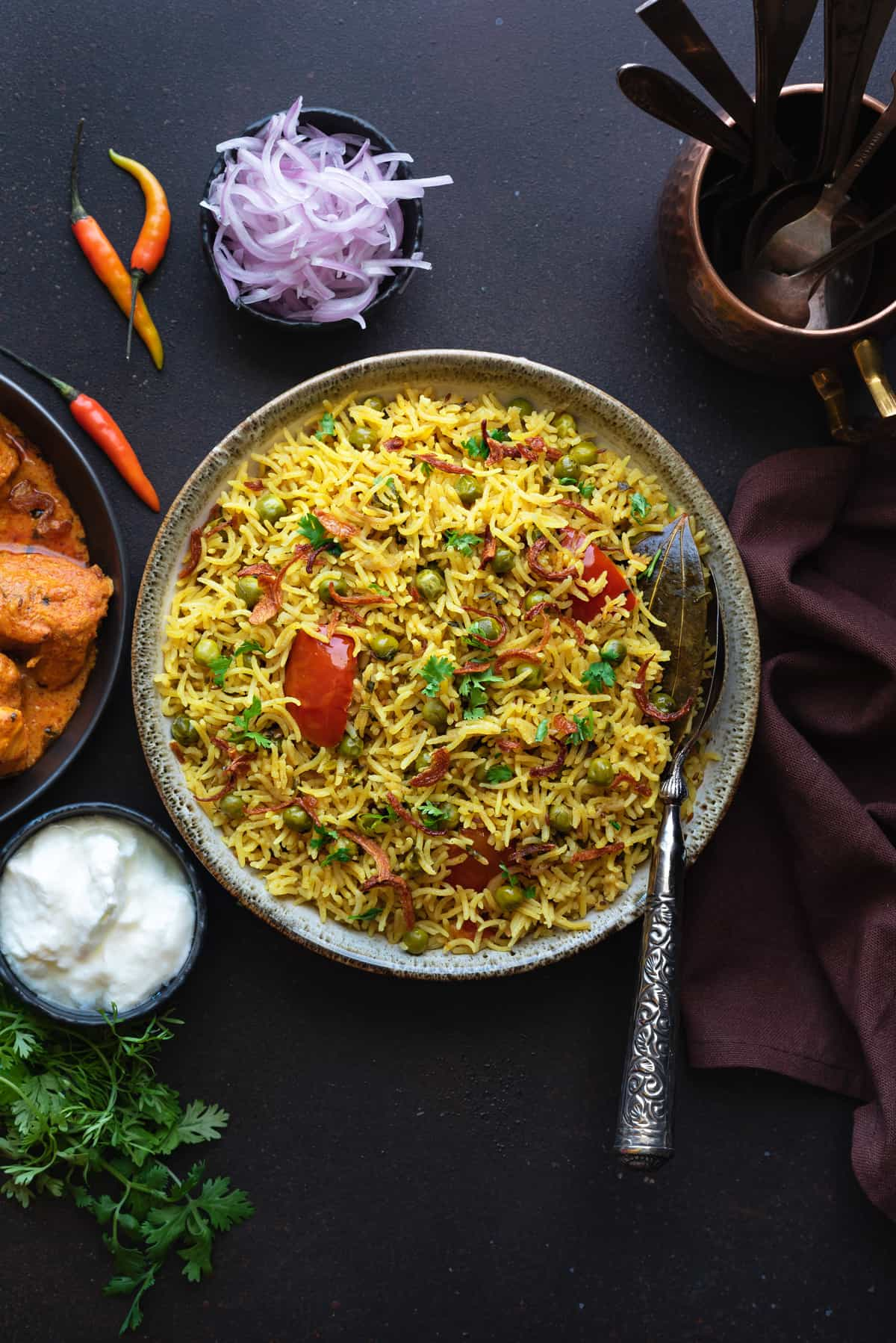 Spicy Matar Pulao in bowl with spoon in it, bowl of curd and curry on side.