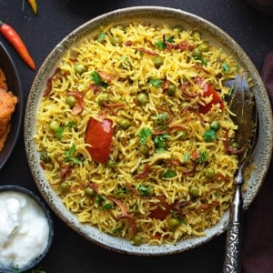 Spicy Instant Pot Matar Pulao served in grey bowl with curd in bowl on side.
