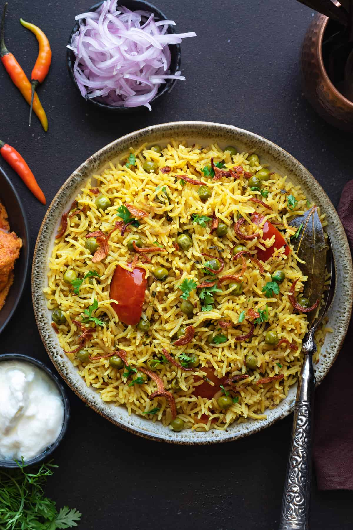 Close up shot of spicy matar pulao in bowl with spoon in it.