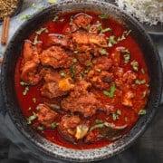 Close up shot of lamb vindaloo curry served in black bowl.