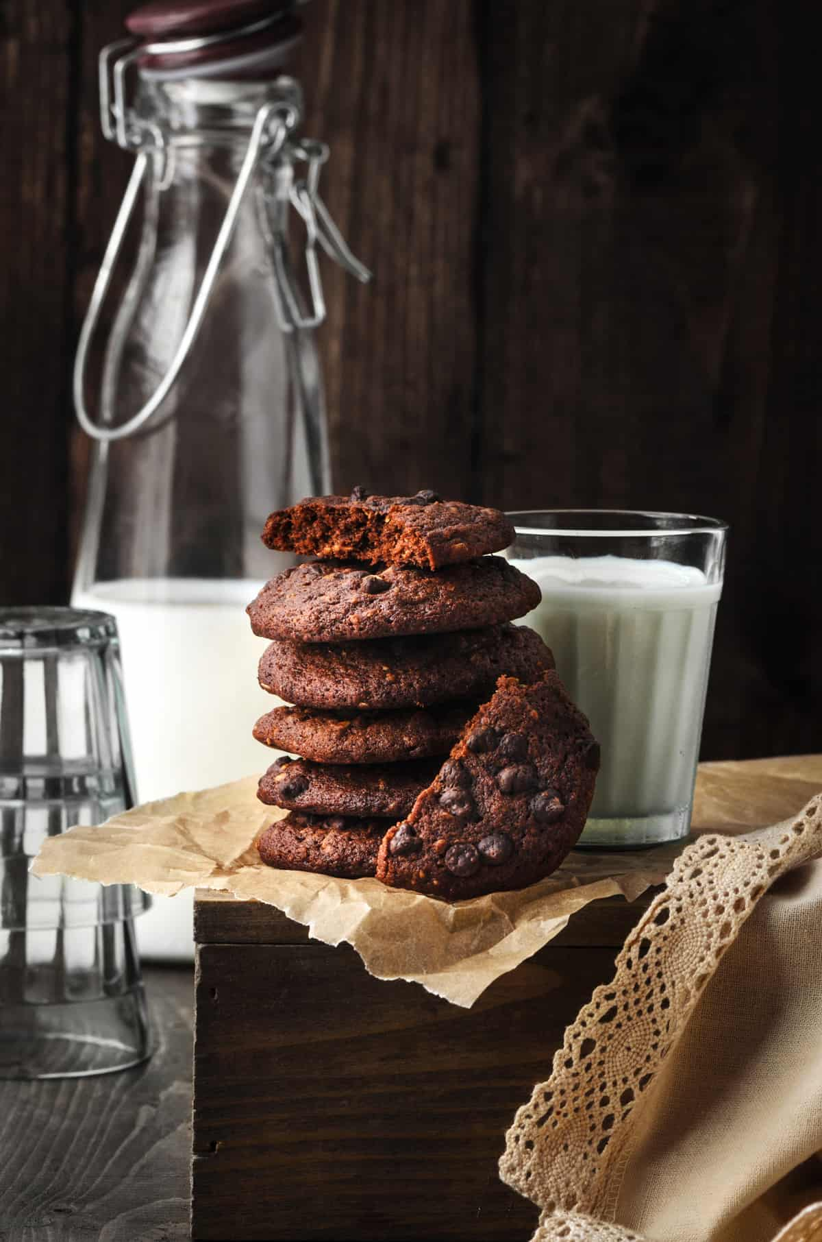 Stacked chocolate chip cookies with a glass of milk bottle and glass at the back.