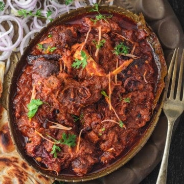 Bhuna Gosht served in brass plate served with parathas on side.