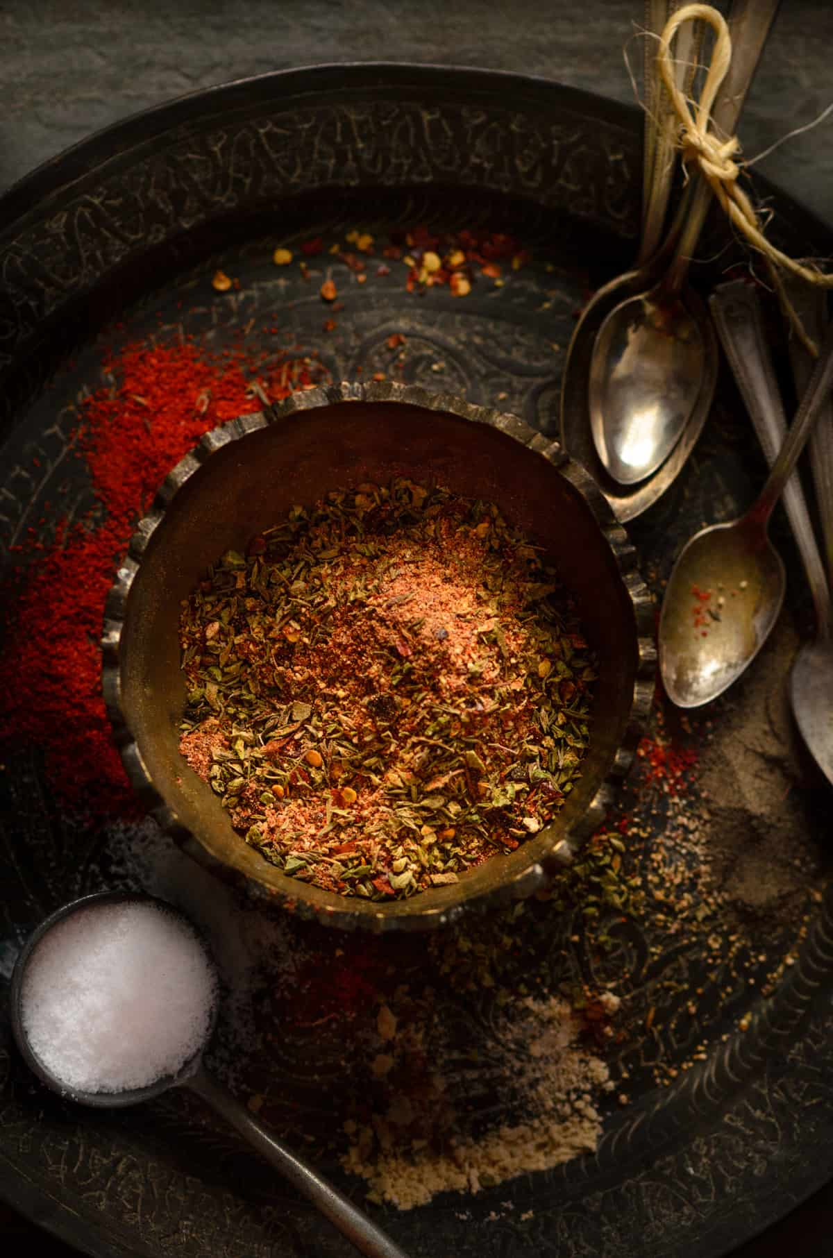 Cajun spice mix in brass bowl kept on plate with salt and spices spread around.
