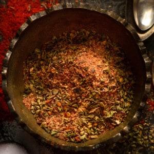 Close up shot of cajun seasoning in brass bowl.