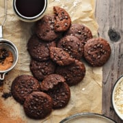 12 chocolate chips oats cookies placed on brown paper with black coffee on side.