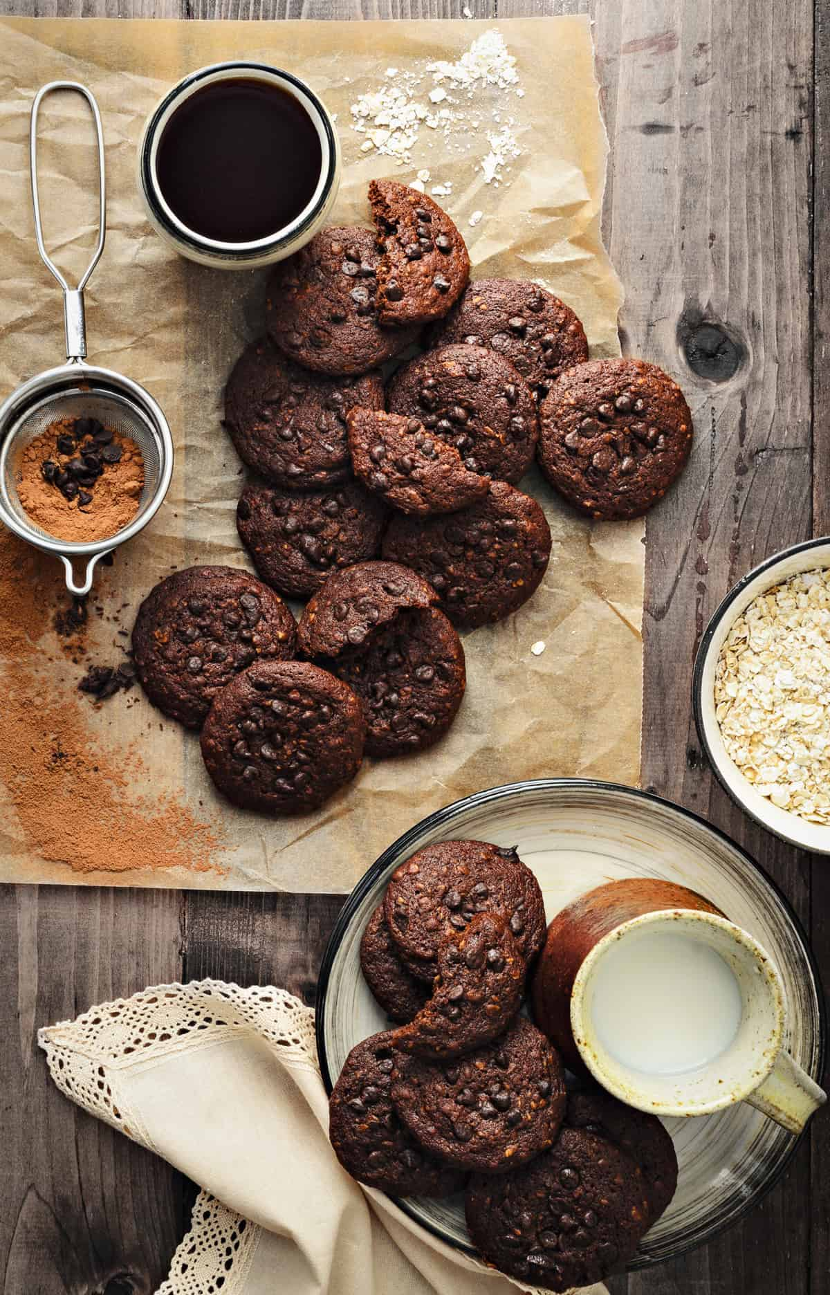 Chocolate Oats cookies on brown paper and plate, with milk, coffee and oats on side.