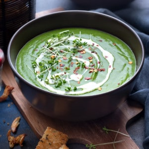 Garnished green pea soup in two brown bowls with croutons on the side.