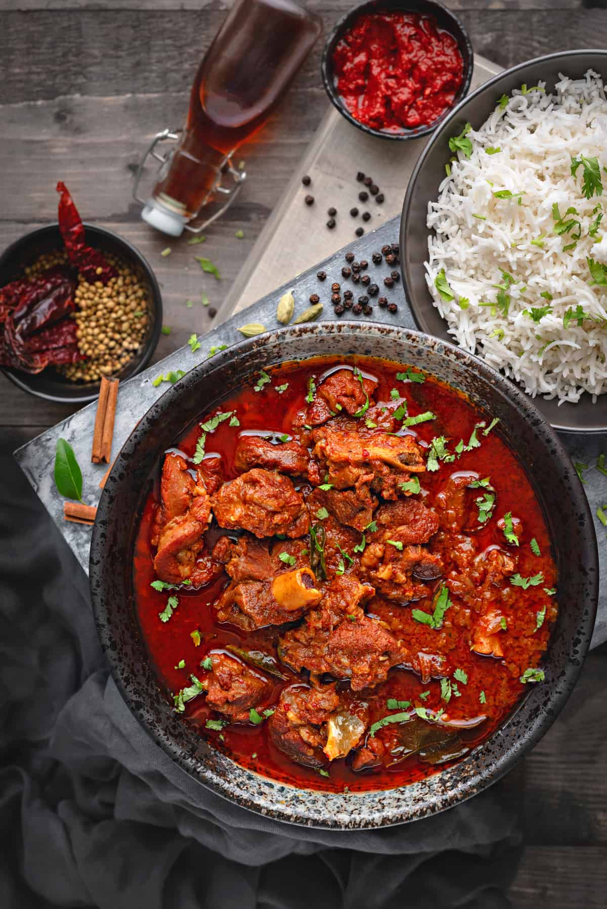 Overhead shot Lamb vindaloo in black bowl along with a bowl of rice on side.