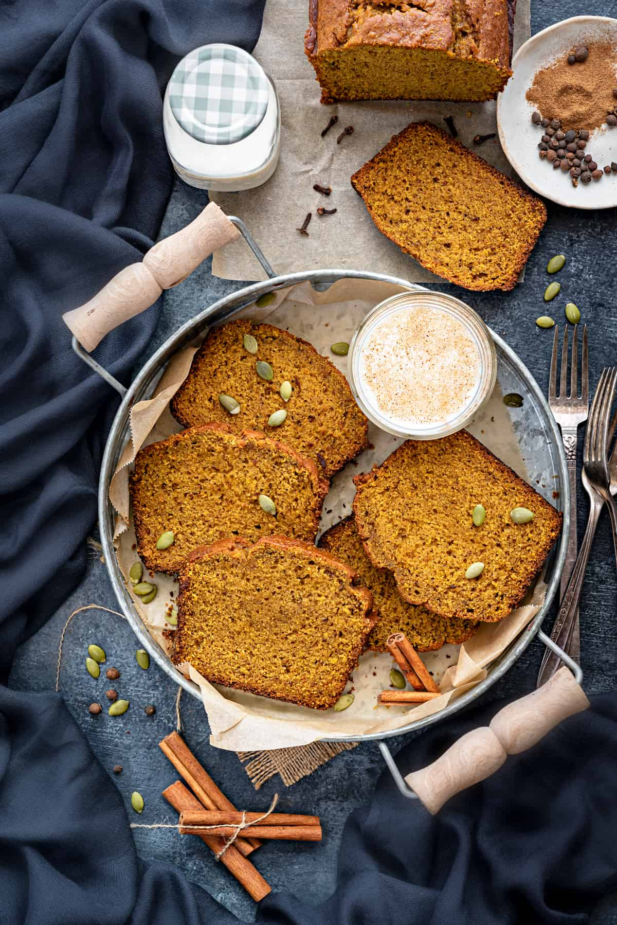 5 Pumpkin Bread slices on round tray with glass of milk and some spices spread around.
