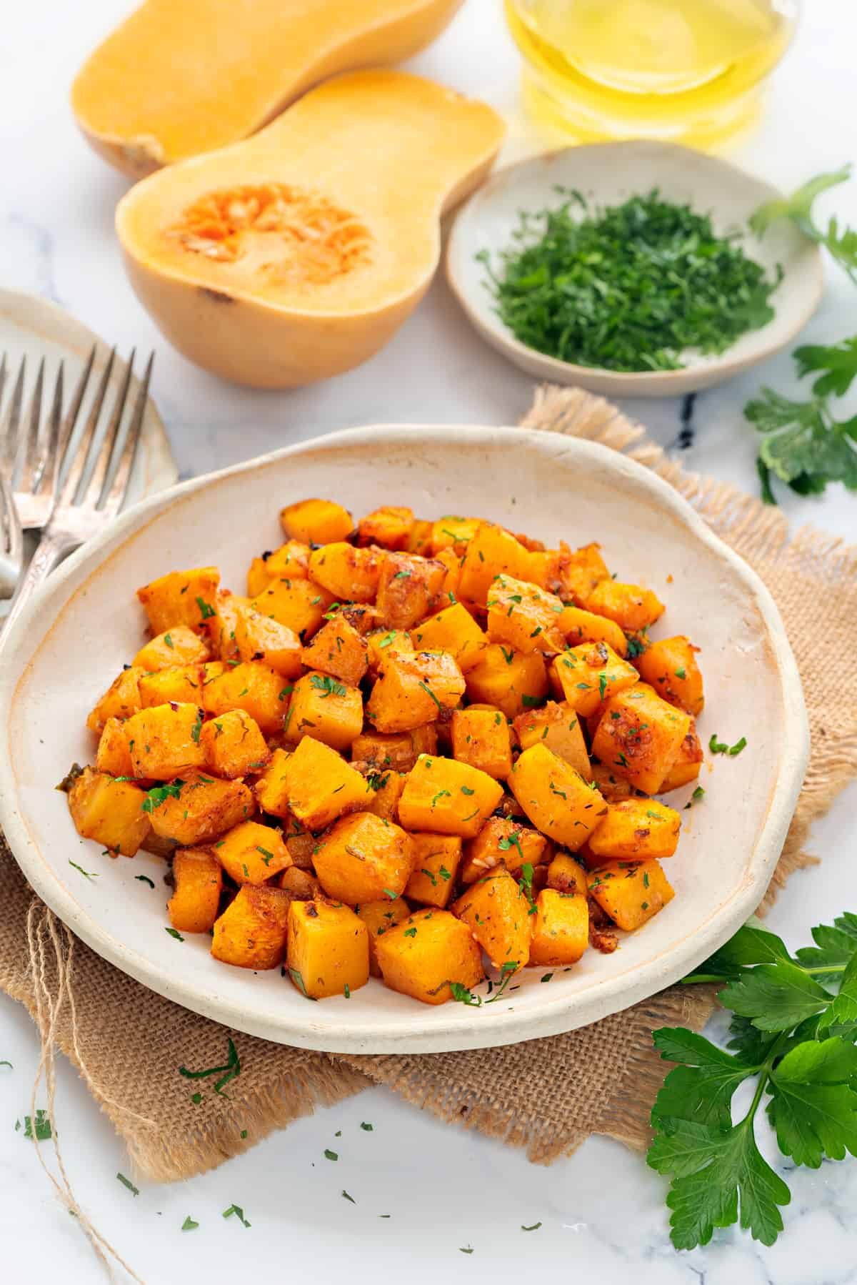 Roasted butternut squash cubes in white ceramic plate, cut squash and parsley placed at the back.