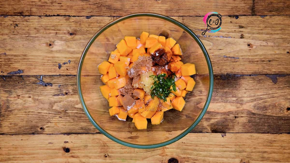 All the savory ingredients added to butternut squash cubes placed in bowl.