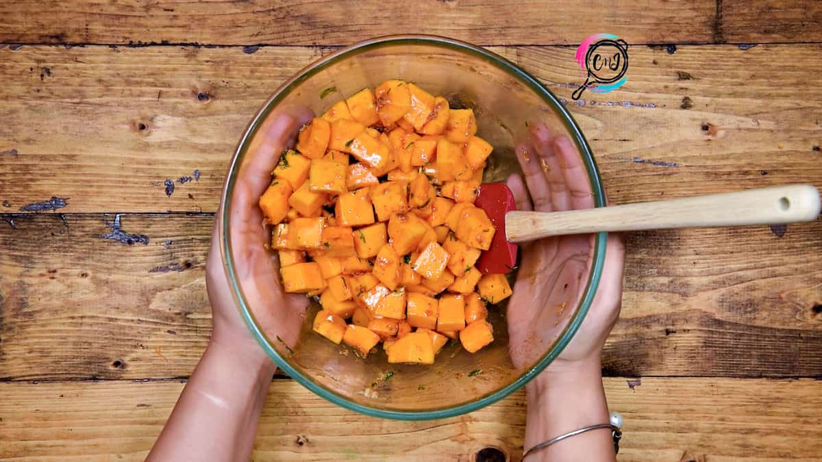 Butternut squash cubes tossed well in seasonings in bowl.