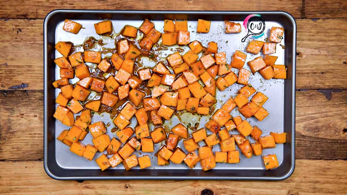 Tossed squash cubes placed on baking sheet in single layer.