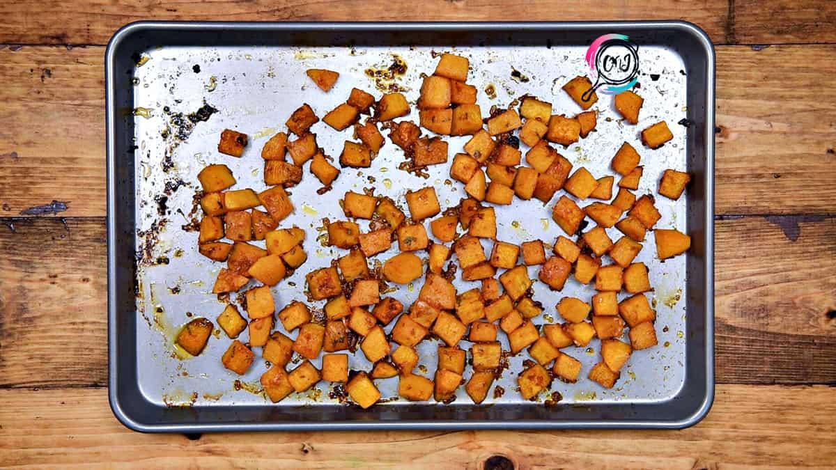 Savory roasted butternut squash cubes in baking sheet pan.