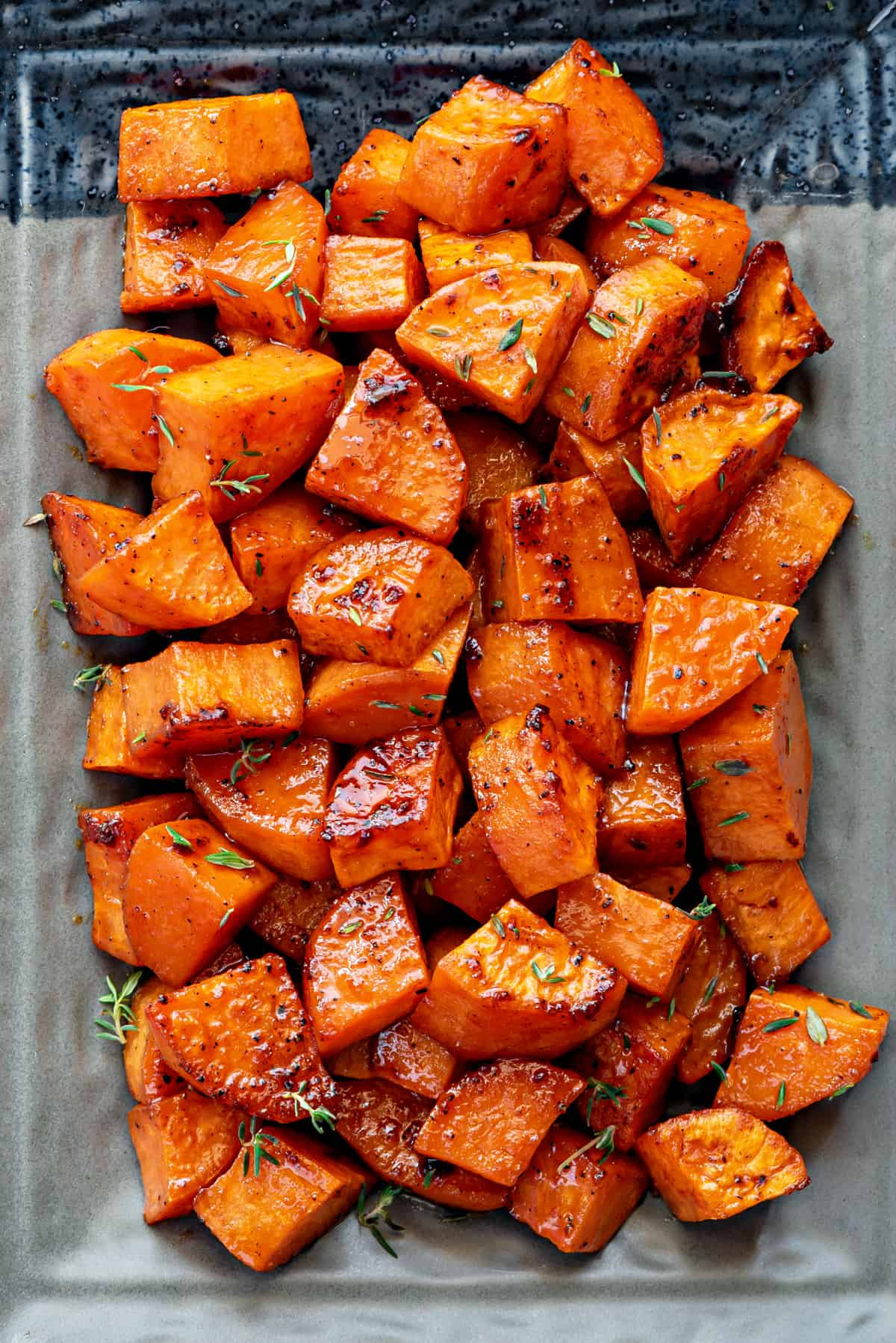A shot from above, of a plate of roasted sweet potatoes with thyme.