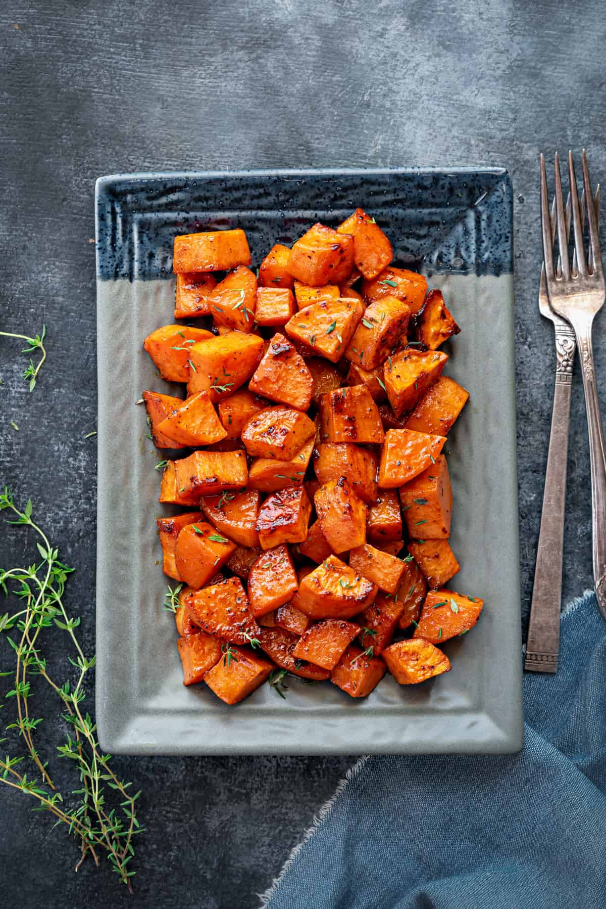 A large plate of roasted sweet potatoes, shot from above, with two forks and sprigs of thyme on the table next to the plate.