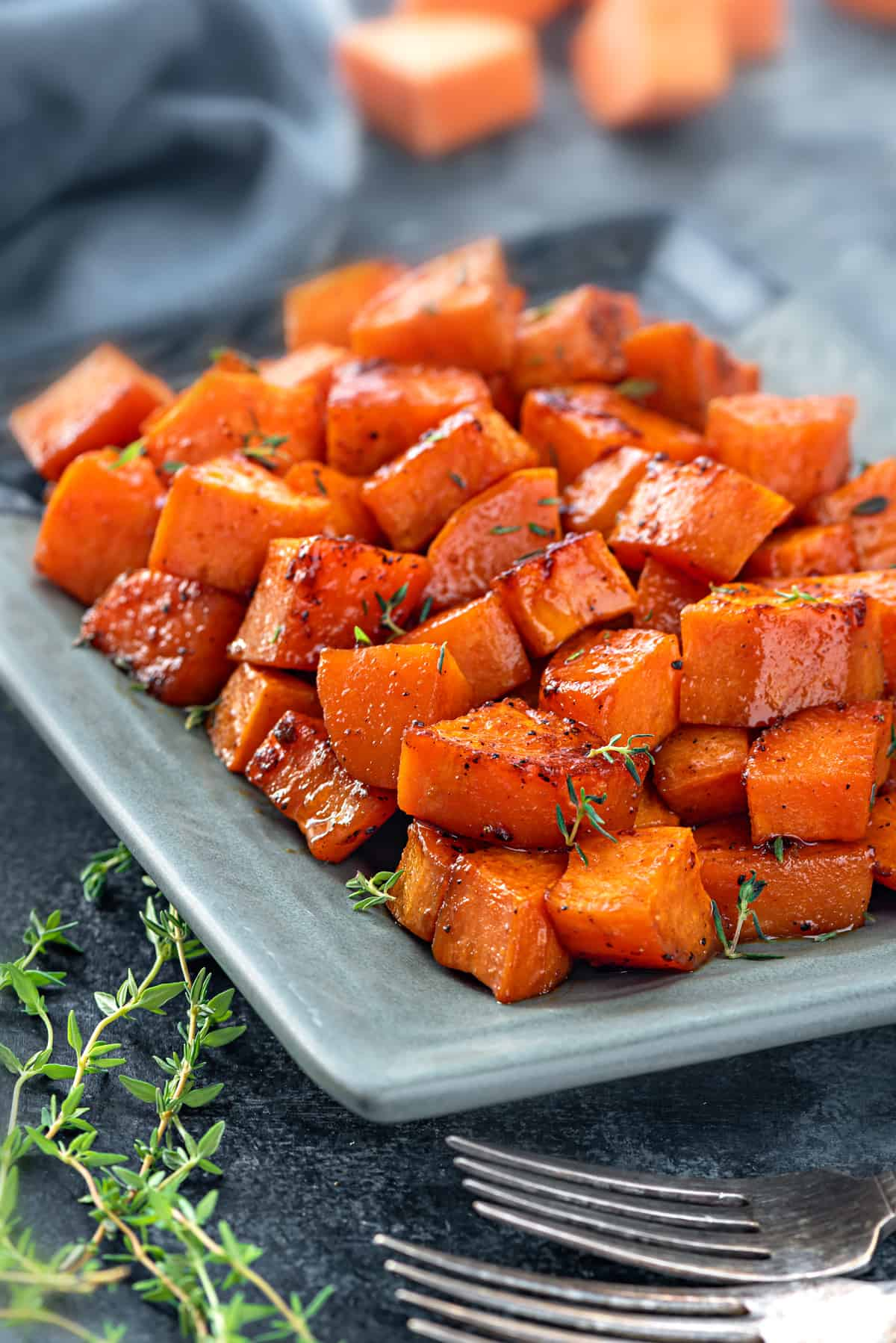 A plate of cubed, caramelized, sweet potatoes with sprigs of thyme on top.