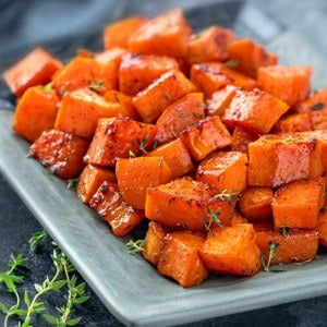 Close up of roasted sweet potatoes served in blue plate.