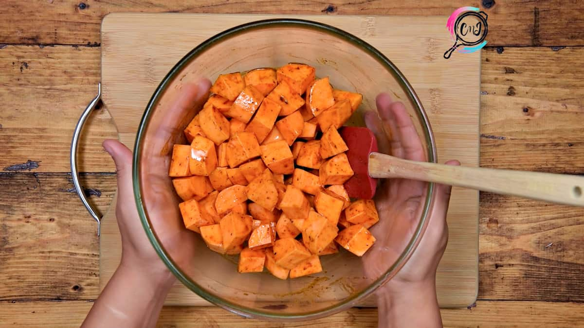 Sweet potato tossed with maple and seasonings in glass bowl.