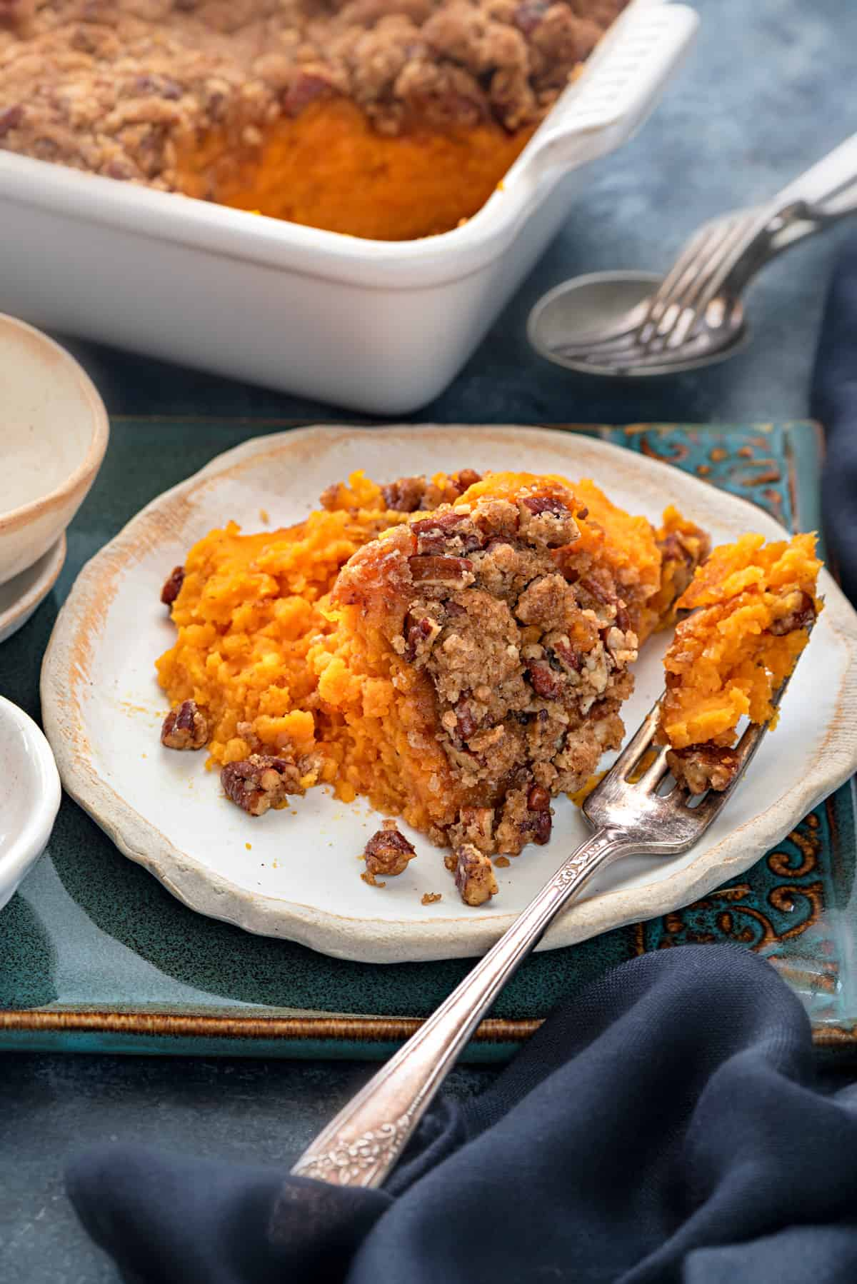 A small ceramic plate with a heaping scoop of sweet potato casserole and fork.