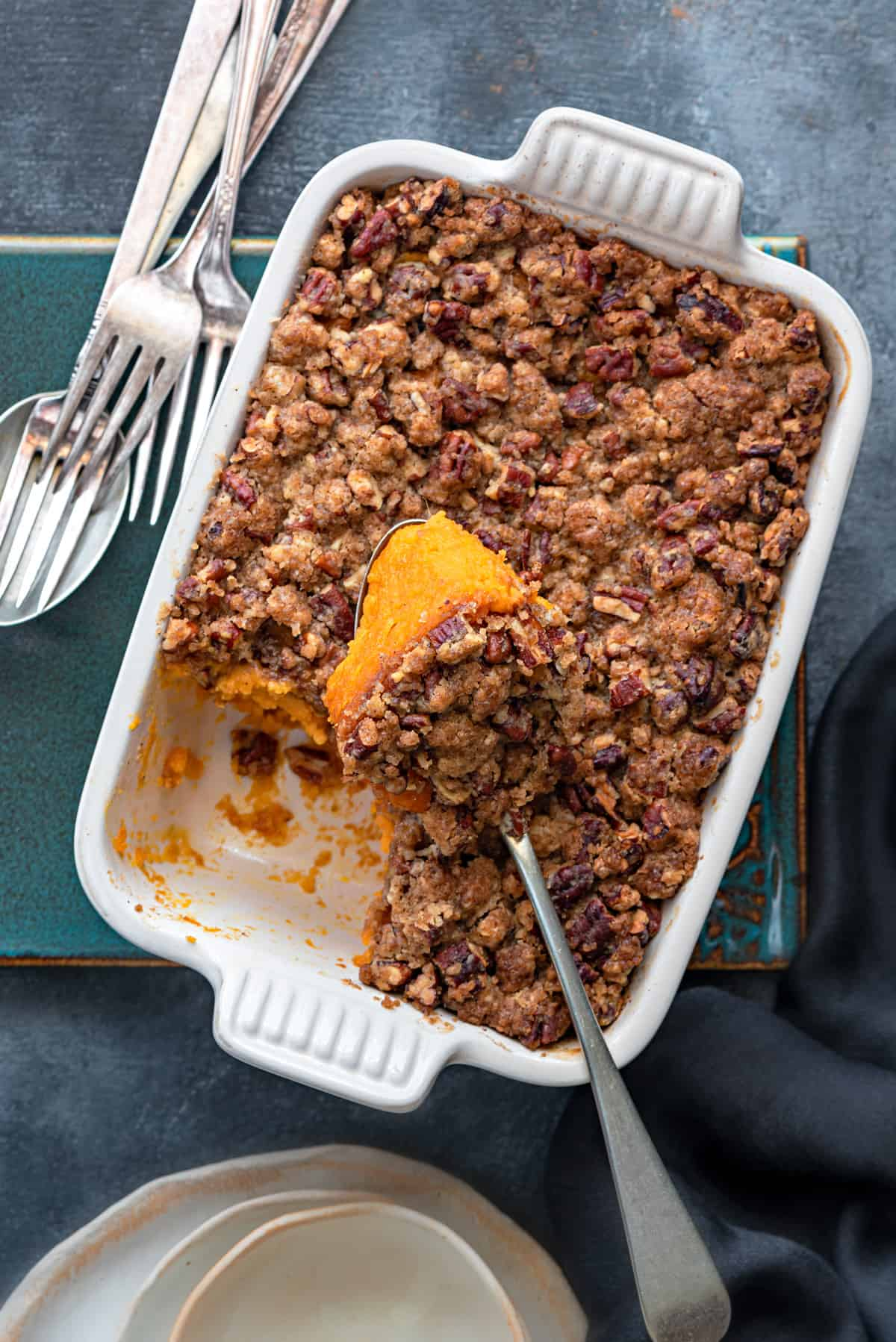Overhead shot of a white casserole dish with scooped sweet potato casserole serving on spoon.