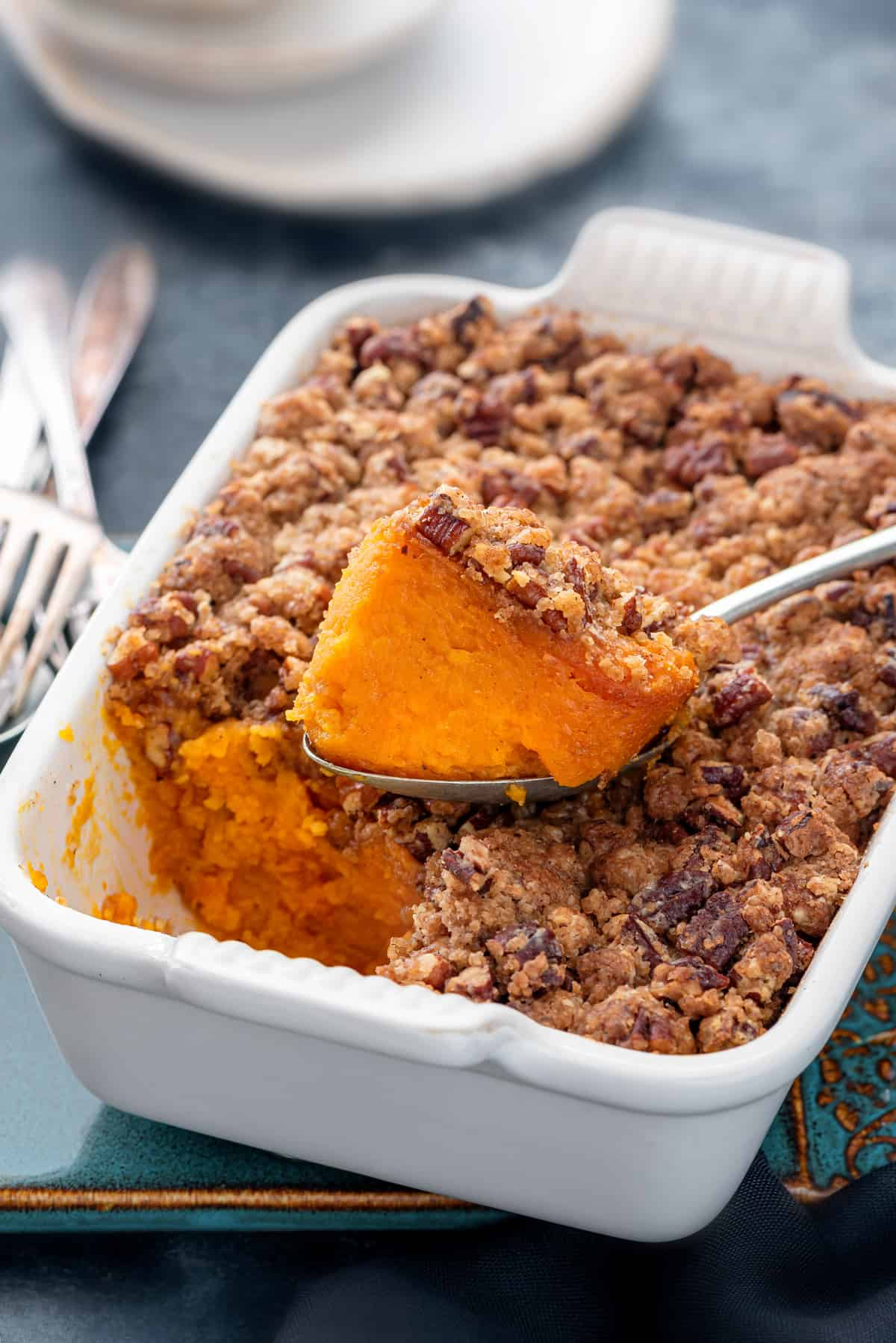 A casserole dish with a large scoop of sweet potato casserole taken out with the spoon.