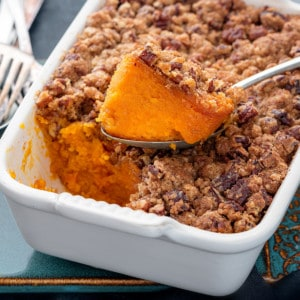 Closeup shot of spoon holding sweet potato casserole that is kept on casserole dish.
