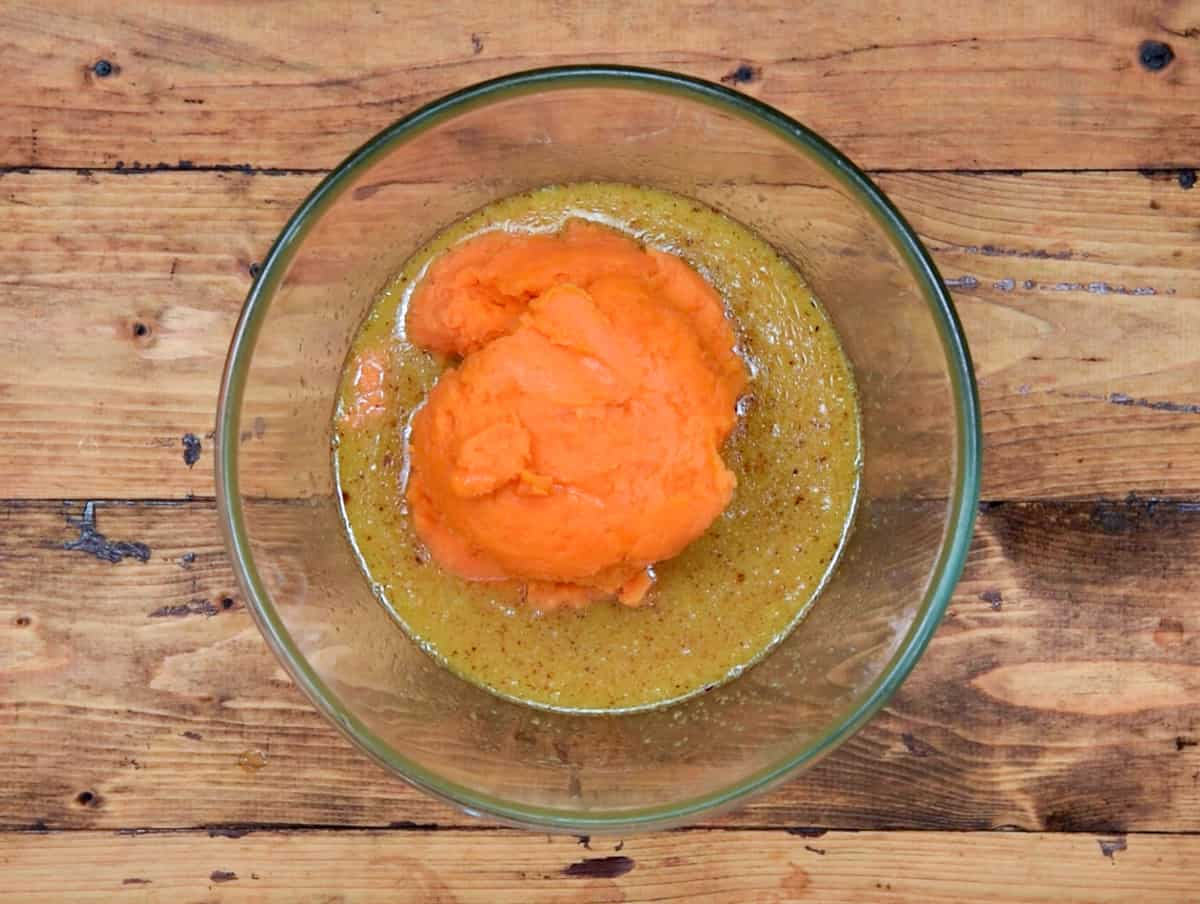 Mashed sweet potatoes added to whisked egg butter mixture in glass bowl.