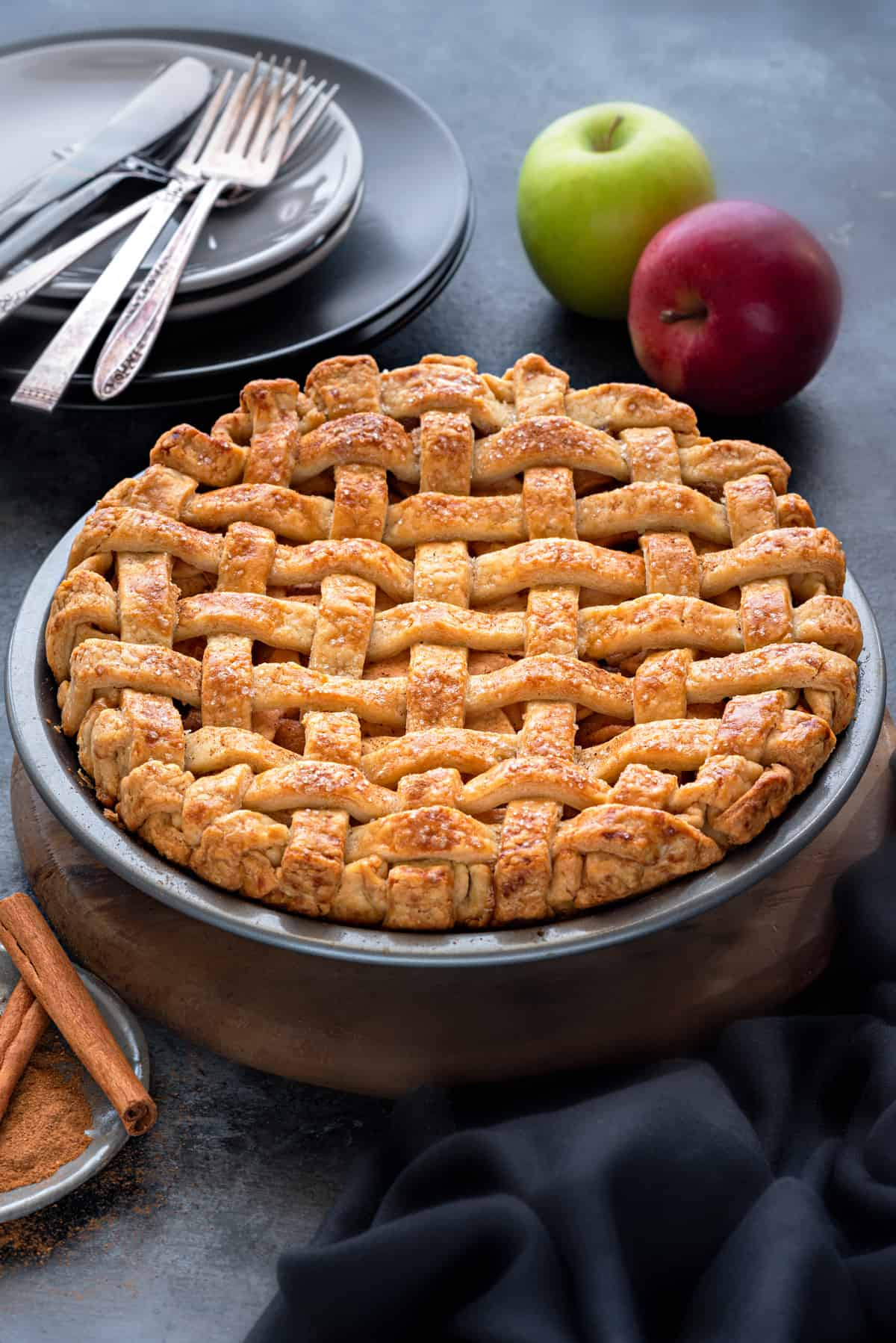 An apple pie with crispy lattice crust, shot from slightly above, apples placed in the background.