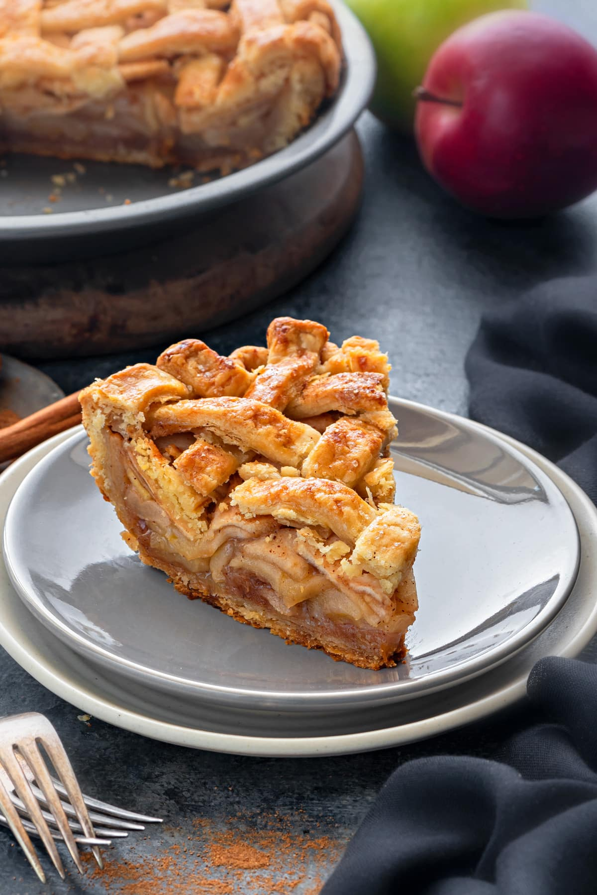 A thick slice of apple pie, with a golden brown lattice top.