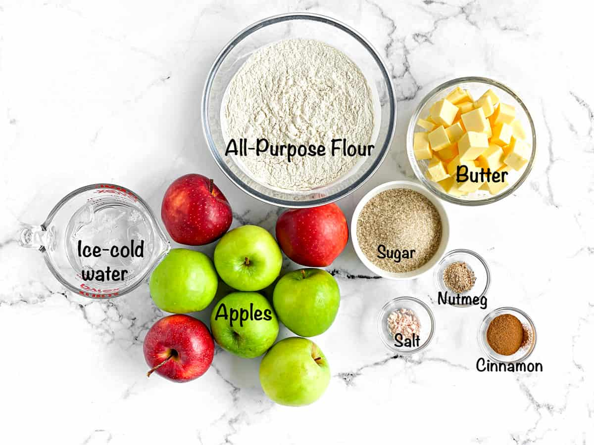 Overhead shot of the ingredients for this pie. Water, apples, flour, butter, sugar, nutmeg, salt, cinnamon.